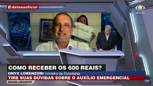 """Ao vivo: Mulher levanta cartaz com dizeres """"GloboLixo"""" durante entrevista de Onyx Lorenzoni cedida ao apresentador Datena"""